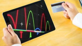 Digital animation of colorful graph pattern on digital tablet screen. Businessman holding a digital tablet and credit card 4k stock video footage