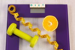Digital bathroom scale with tape measure, orange, dumbbells, slimming concept Stock Photography