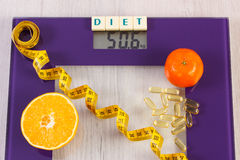 Digital bathroom scale with tape measure, tablets, fruits, slimming concept Royalty Free Stock Photo