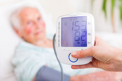Digital Blood Pressure And Heart Rate Measuring. Nurse registering sick elderly patient's systolic and diastolic blood pressure in bed with the heart rate Stock Photo
