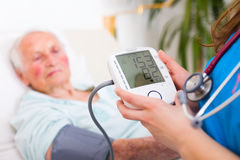 Digital Blood Pressure Measuring. Nurse registering sick elderly patient's systolic and diastolic blood pressure in bed with the heart rate Stock Photography