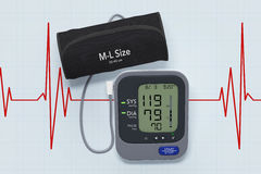 Digital Blood Pressure Monitor with Cuff  on Cardiogram Backgrou Stock Photos