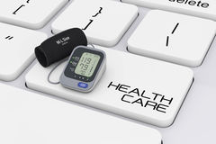 Digital Blood Pressure Monitor with Cuff over Computer Keyboard Stock Photo