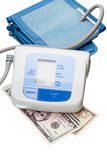 Digital blood pressure monitor and dollar cash Stock Photos