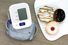 Digital-Blutdruck-Monitor und Donut, ungesundes Lebensmittel Stockfotografie