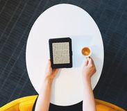 Digital book reader and coffee on oval table. Top down view on small digital ebook reader and coffee in hands of person Royalty Free Stock Images