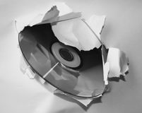Digital break-through. The CD at the large hole in the white paper Stock Photography