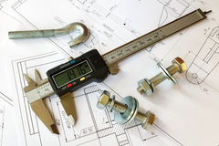 Digital caliper with bolts and nuts on engineering drawings stock images