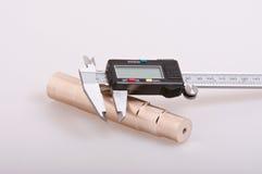 Digital caliper & bronze spigot. Electronic digital calipers resting on a turned bronze spigot Stock Photo