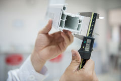 Digital caliper measurement. The laboratory technician measures the plastic profile with a digital caliper. application of digital caliper close-up royalty free stock image