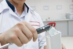 Digital caliper measurement. The laboratory technician measures the plastic profile with a digital caliper. the worker conducts measurements with a digital stock image