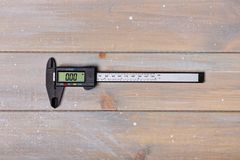 Digital caliper on table. Closed digital caliper lies in the middle of a wooden table stock photos