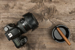 Digital camera and ashtray with a cigar on an old wood. Royalty Free Stock Photo
