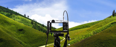 Digital camera on camera tripod taking a photo of panoramic green hills landscape, selective focus on camera Stock Photo