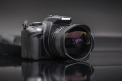 Digital camera with fish eye lens. On a textured black surface Royalty Free Stock Photography