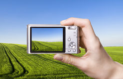 Digital camera in hand. Landscape Royalty Free Stock Images