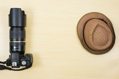 Digital camera and hat on wood table for travel Royalty Free Stock Photos