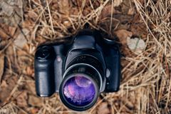 Digital camera lies on dry grass royalty free stock photography
