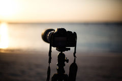 Digital camera. A digital camera mounted on a tripod, in the process of shooting the sunset in the ocean royalty free stock photos