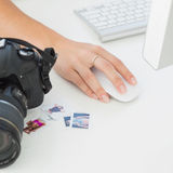 Digital camera on photographers desk with womans hand on mouse Royalty Free Stock Images