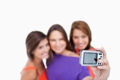 Digital camera photographing three teenagers Stock Photography