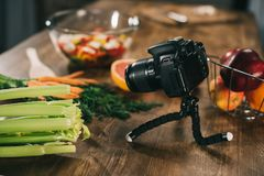 Digital camera and vegetables. On wooden tabletop stock photo