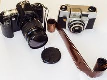 Digital camera verses film camera. One digital camera and one film camera with a roll of film Stock Photography