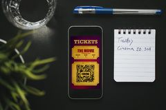 Digital cinema tickets in a smartphone screen, and handwritten text with date notes. Electronic cinema tickets in a mobile phone screen Stock Photo