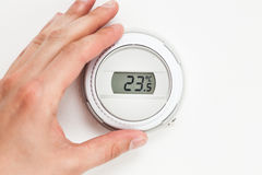 Digital climate thermostat controlling by hand. Closeup view Stock Images