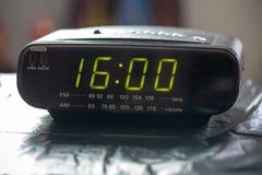 Digital clock closeup displaying 16:00 o`clock. Black digital alarm radio clock.Alarm radio clock indicating time to wake up royalty free stock image