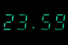 Digital clock in green. Isolated black Royalty Free Stock Photo