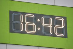 Digital clock on wall. Green background. City stock photos