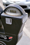 Digital Coin Parking Meter. Coin fed digital parking meter.  Digital readout is visible with front end of car blurred in background Stock Image
