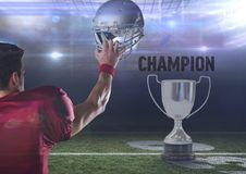 American football  player holding up helmet with throphy and  text Royalty Free Stock Image