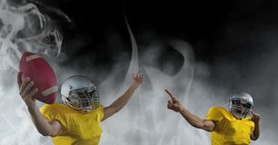 American football players cheering in smoke. Digital composite of American football players cheering in smoke Royalty Free Stock Image