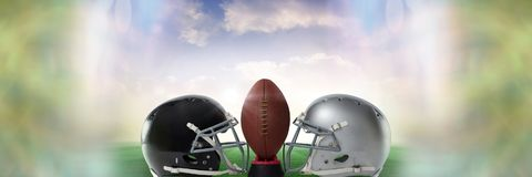 American football versus team helmets with ball with sky transition royalty free stock images