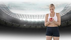Athletic woman in a stadium. Digital composite of an athletic Caucasian woman holding a red ball inside a stadium stock video