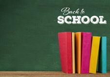 Back to school text on blackboard and Desk with books. Digital composite of Back to school text on blackboard and Desk with books Royalty Free Stock Photography