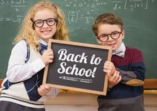 Back to school text on blackboard with two school kids Royalty Free Stock Image