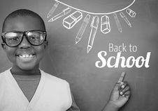 Back to School text and stationery on blackboard with boy. Digital composite of Back to School text and stationery on blackboard with boy Royalty Free Stock Photos