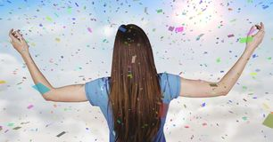 Back of woman with arms outstretched against sunny sky and confetti. Digital composite of Back of woman with arms outstretched against sunny sky and confetti Royalty Free Stock Photo
