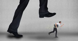 Big business man trying to step on a small business man. Digital composite of Big business man trying to step on a small business man stock image