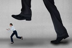 Big business man trying to step on a small business woman. Digital composite of Big business man trying to step on a small business woman Stock Photography