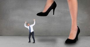 Big business woman trying to step on a small business man. Digital composite of Big business woman trying to step on a small business man stock photo