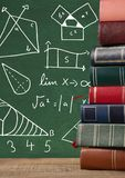 Books on Desk with blackboard graphics of math diagrams. Digital composite of Books on Desk with blackboard graphics of math diagrams royalty free stock photos