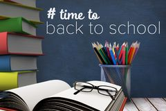 Books on the table against blue blackboard with back to school text Stock Images
