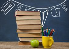 Books on the table against blue blackboard with graphics. Digital composite of Books on the table against blue blackboard with graphics Royalty Free Stock Photography