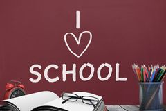 Books on the table against red blackboard with I love school text royalty free illustration