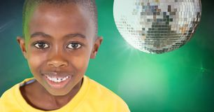 Boy against green background with disco ball party. Digital composite of Boy against green background with disco ball party Royalty Free Stock Images