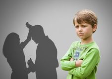 Boy against grey background with arms crossed concerned and parents arguing violently Stock Image